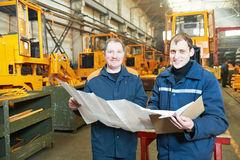 Experienced industrial assembler workers. Adult experienced industrial workers examining technical drawing during heavy industry machinery assembling on Stock Image
