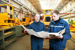 Experienced industrial assembler workers. Adult experienced industrial workers examining technical drawing during heavy industry machinery assembling on Royalty Free Stock Photos