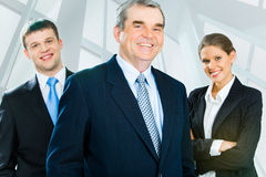 Experienced leader. Portrait of senior boss looking at camera with smile with his business team standing on each side of him stock image