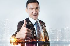Experienced leader raising thumb up. Brilliant career. Close up of smiling experienced leader standing in front of you while raising his thumb up royalty free stock images