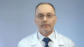Experienced look of serious male physician, professional medical aid at clinic royalty free stock image