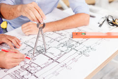 Experienced male architects are working at project. Close up of arms of two engineers projecting a new construction. They are sitting at the table and working Stock Photo