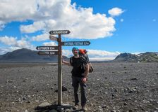 Experienced hiker with heavy backpack staying next to navigation signpost and enjoying beautiful scenery of volcanic mountains and. Experienced male bearded royalty free stock image