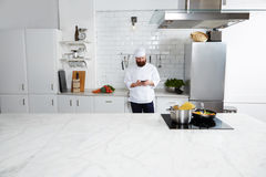 Experienced male chef cook standing on big modern kitchen while using smart phone Royalty Free Stock Photos