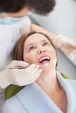 Experienced male dental doctor is treating his patient Royalty Free Stock Images