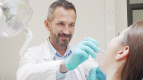 Experienced male dentist smiling while checking teeth of a patient stock footage