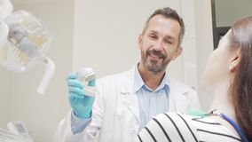 Experienced male dentist talking to his female patient stock footage