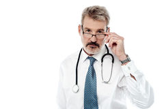 Experienced male doctor isolated over white. Mature male physician adjusting his eye glass stock images