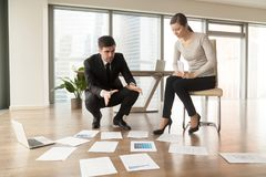 Architect explaining construction plan to client. Experienced male and female interior designers examining apartment drawings, picking colors, analyzing Royalty Free Stock Photo