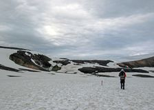 Experienced male hiker hiking alone into the wild admiring geothermal landscape covered with snow, heavy backpack. Travel royalty free stock photography
