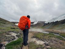 Experienced male hiker hiking alone into the wild admiring geothermal landscape of steaming ground with big, heavy backpack. Experienced male hiker hiking alone royalty free stock images