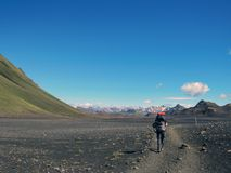 Experienced male hiker hiking alone into the wild with heavy backpack in black desert, Laugavegur hiking trail, Iceland. Beautiful inspirational landscape stock images