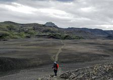 Experienced male hiker hiking alone into the wild with heavy backpack in black desert, Laugavegur hiking trail, Iceland stock photos
