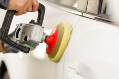 Experienced male mechanic is burnishing the. Close up of hands of man polishing the car Royalty Free Stock Photography
