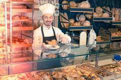 Experienced male pastry maker demonstrating croissant stock photography