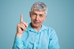 Experienced male pensioner in formal shirt raises fore finger as get brilliant idea for coming weekends, has confident look, isola. Ted over light blue Royalty Free Stock Image