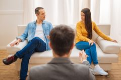 Experienced male psychologist proposing make peace. Little progress. Skillful male psychologist turning with his back while stretching hand to the pleasant stock image
