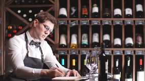 Male wine steward looks at bottles of wine and writing in notebook at wine store. Experienced male wine steward doing stocktaking of wine at store, writing in stock video footage