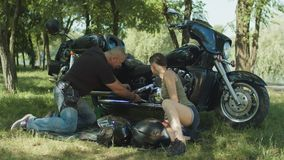 Two bikers repairing motorcycle on park lawn stock footage