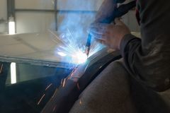 Experienced man performs work on body repair car with a welding machine. Repair of the roof of the vehicle royalty free stock photography