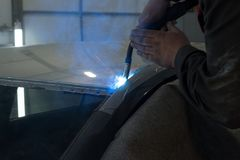 Experienced man performs work on body repair car with a welding machine. Repair of the roof of the vehicle stock photo