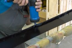 An experienced man in working clothes applies a black sealant stock photos