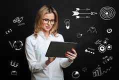 Experienced manager feeling interested while looking at the screen of her tablet. Smart manager. Calm clever responsible employee feeling interested while Royalty Free Stock Image