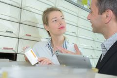 Experienced manager pharmacist counseling female co-worker in modern pharmacy stock photos
