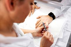Experienced manicurist filing the nails and making their shape and edges just right. Men's manicure stock images