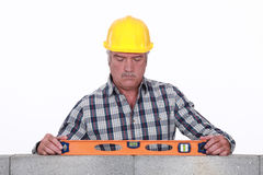 Experienced mason. Checking wall is level royalty free stock images