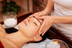 Experienced masseuse in white t-shirt making relaxing massage for face. Completely comfortable. Experienced masseuse in white t-shirt making relaxing massage for royalty free stock photo