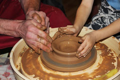 experienced master potter teaches the art of making pots  clay on the 's wheel Royalty Free Stock Image