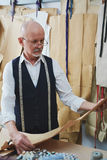 Experienced Mature Tailor Working in Atelier. Portrait of experienced old tailor looking at patterns while making clothes in atelier shop Stock Photo