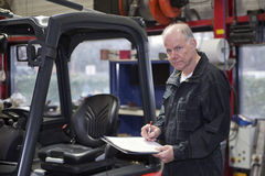 Experienced mechanic going over a checklist. Experienced Mechanic working through a checklist before a brand new forklift is delivered and commissioned in a royalty free stock photos