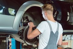 Experienced mechanic replacing the disk brakes of a car in a mod. Experienced auto mechanic replacing the disk brakes of a lifted car during work in a modern stock photo