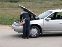 Experienced Mechanic Under the Hood. Mechanic checks out car under hood Stock Image