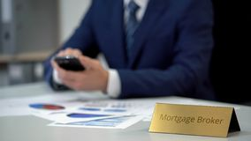Experienced mortgage broker using mobile app, studying situation on market. Stock photo stock image