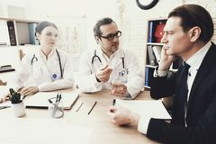 Experienced neurologist diagnoses male patient with headache at medical office. royalty free stock image