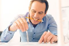 Experienced nice architect holding a pencil. Architechture drawing. Experienced professional nice architect holding a pencil and doing a drawing while working in royalty free stock photography