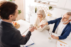 Experienced notary having meeting with aged couple of clients Stock Photos
