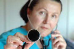 Experienced nurse with a steth. Nurse performing a checkup with a stethoscope; selective focus on the hand holding the apparatus Royalty Free Stock Image