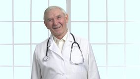Experienced old senior doctor with stethoscope. Laughing hard, very funny. Bright checkered framed windows background stock video