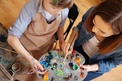 Experienced painter teaching kid in the art studio. Creating masterpiece together. Proficient involved experienced painter sitting in the studio and conducting royalty free stock photography