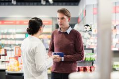 Experienced pharmacist checking the indications of a medicine. Experienced female pharmacist checking the indications and contraindications of a new medicine stock photo