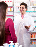 Experienced pharmacist counseling female customer. Cheerful experienced pharmacist counseling female customer stock photography