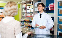 Experienced pharmacist counseling female customer in farmacy. Experienced friendly smiling pharmacist counseling female customer in modern farmacy stock images