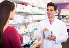 Experienced pharmacist counseling female customer Stock Image