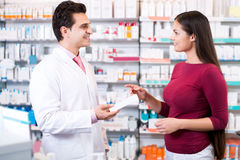 Experienced pharmacist counseling female customer. In modern farmacy stock image