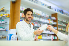 Experienced pharmacist counseling female customer royalty free stock photography