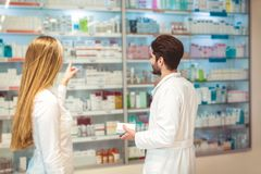 Experienced pharmacist counseling female customer in pharmacy royalty free stock images